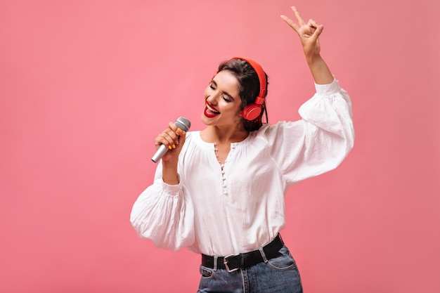 Attractive girl in red headphones singing in microphone on pink background.  pretty lady with dark hair in white stylish blouse is listening to music.