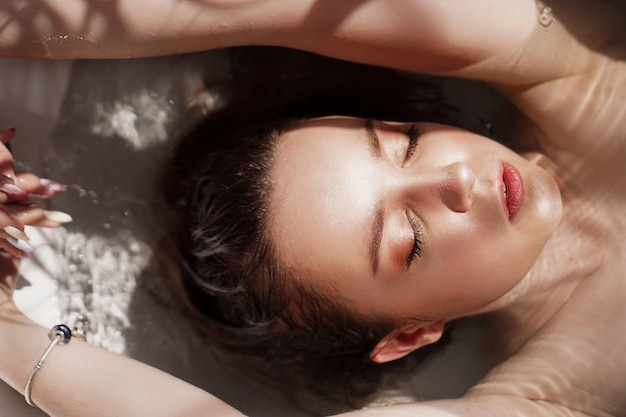 An attractive girl relaxing in bath with closed eyes on light surface