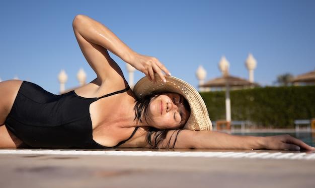 麦わら帽子と水着を着て太陽の下で休んでいる魅力的な女の子。暖かい国での休暇とレクリエーションの概念。