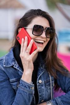 Привлекательная девушка отдыхает на природе в выходные дни. девушка в джинсовой куртке, сидя в парке. кавказская брюнетка молодая женщина, говорить на смартфоне за пределами одного. технологии и гаджеты.