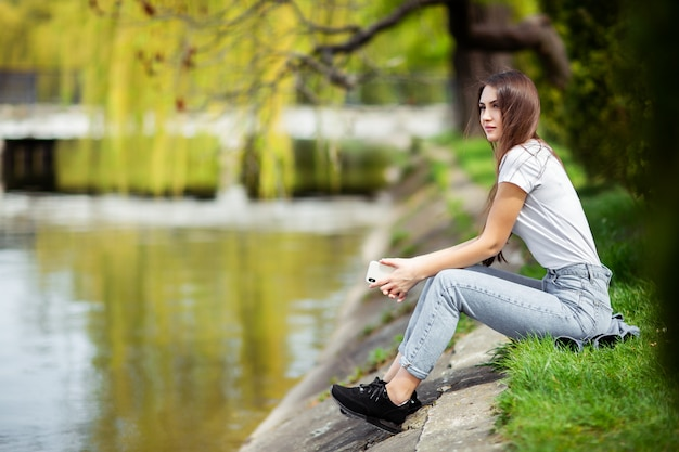 Attractive girl resting on riverbank near forest at spring warm day. relaxing on nature at weekend. girl in jeans clothes sitting near the lake in park. nature concept. fashion photoshoot. horizontal.