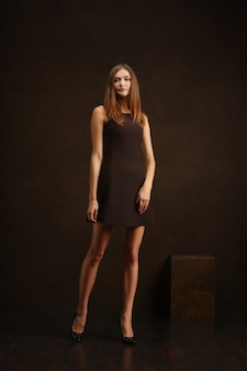 Attractive girl in short dress posing near dark wall in provocative manner