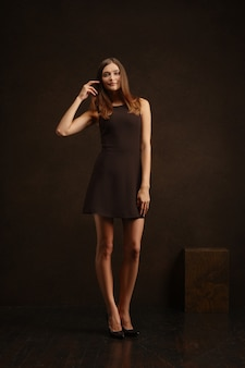 Attractive girl in short dress touching her long hair. full length low key portrait.