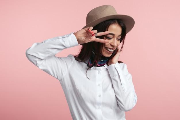 Привлекательная девушка показывает знак v и счастливо улыбается над розовой студией