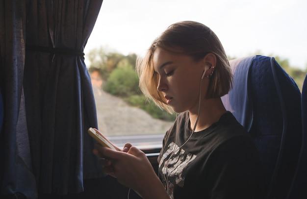 매력적인 여자는 창 근처 버스에 앉아 음악을 듣고 스마트 폰을 사용
