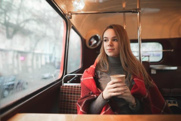 Привлекательная девушка сидит в ретро-кафе и смотрит в окно