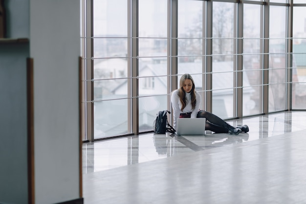 Attractive girl sitting on floor with laptop and things in airport terminal or office. travel atmosphere or alternative work atmosphere.