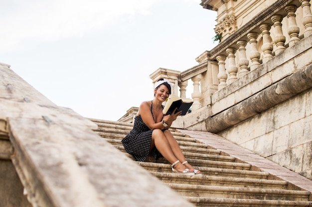 Attractive girl sitting on stairs and reading book.