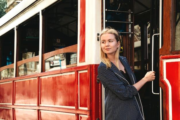 路上で赤いレトロな路面電車の戸口に立っている魅力的な女の子