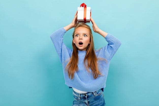 魅力的な女の子が赤いリボンで彼女の頭にギフトを壁に立っています。