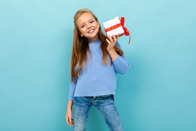 Attractive girl stands by the wall with a gift with a red ribbon