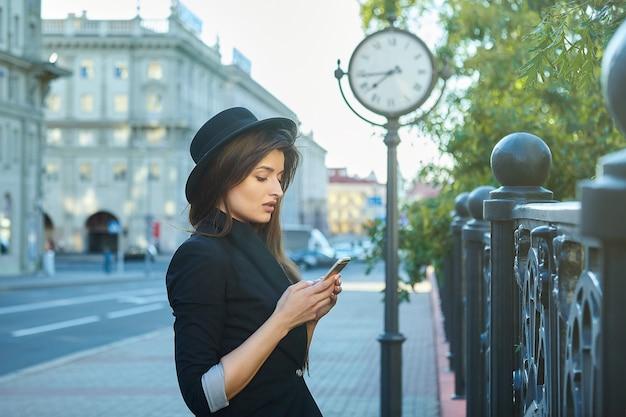 大都市の時計の前に立っている魅力的な女の子