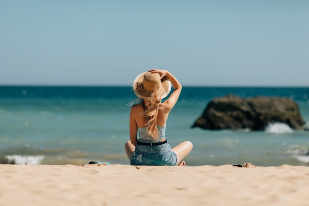 Attractive girl in sunglasses and hat lies on warm sand