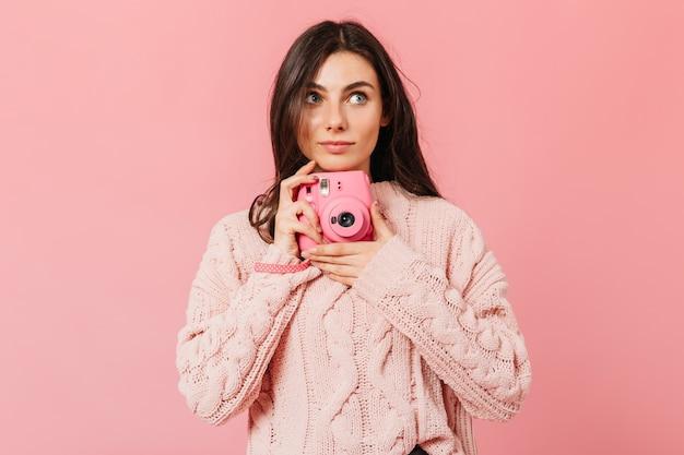 Ragazza attraente scatta foto sulla fotocamera instax. signora in maglione rosa cerca su sfondo isolato.