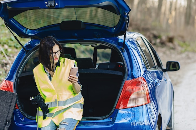 Attractive girl talking by phone near car on road in safety jacket