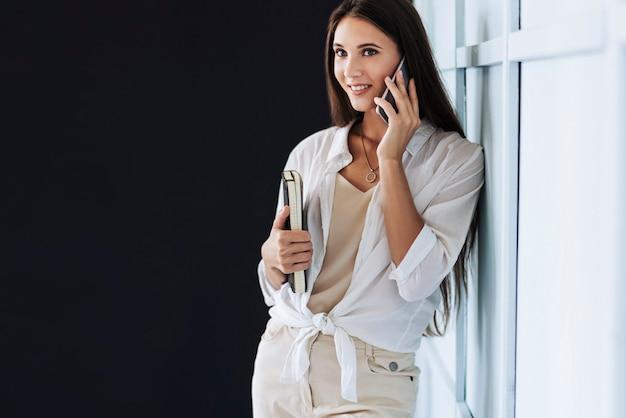 매력적인 여자 스마트 폰에 검은 메모장을 들고. 아름 다운 소녀 작업에 대 한 휴대 전화를 사용