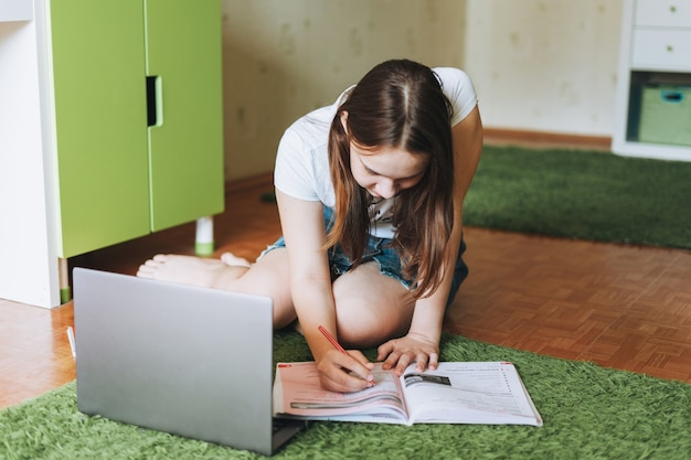 Attractive girl teenager do homework learn foreign language writing in pupil book with opened laptop at the room home dictance education