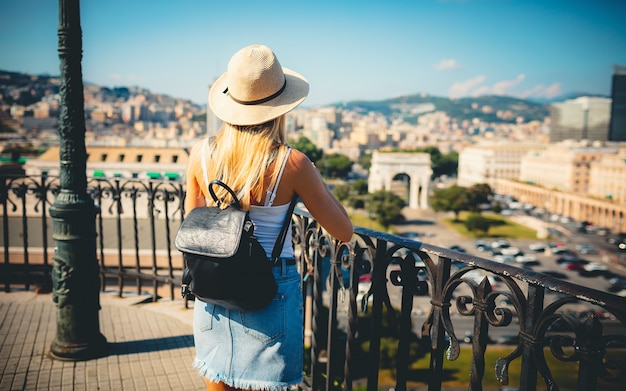 Attractive girl tourist in hat with backpack exploring new city in europe at summer and using her phone to take photo