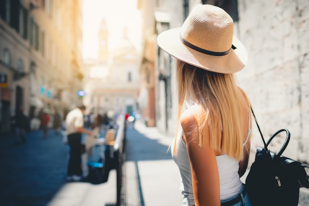 Attractive girl tourist in hat with backpack exploring new city in europe at summer