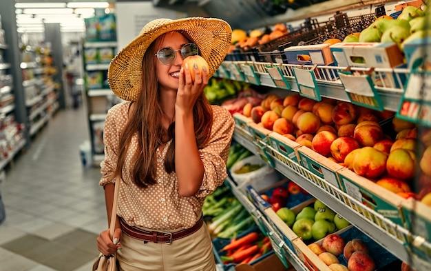 ブラウス、サングラス、麦わら帽子をかぶった魅力的な女の子の観光客が果物を買います。観光、旅行、レジャーの概念。