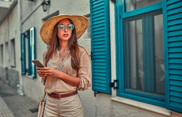 블라우스, 선글라스와 밀짚 모자에 매력적인 여자 관광은 파란색 셔터가있는 집의 배경에 스마트 폰을 사용합니다. 관광, 여행, 레저의 개념.