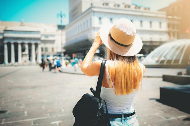 Привлекательная девушка турист в шляпе с рюкзаком, исследуя новый город в европе летом и используя свой телефон, чтобы сфотографировать