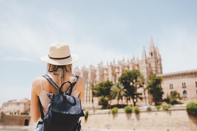 Привлекательная девушка турист в шляпе с рюкзаком, исследуя новый город в европе летом