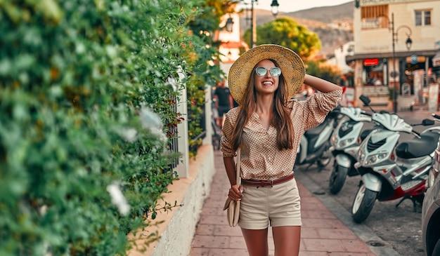 Привлекательная туристка в солнечных очках, блузке и соломенной шляпе гуляет по улицам города на фоне стоянки для скутеров. понятие о туризме, путешествиях, отдыхе.