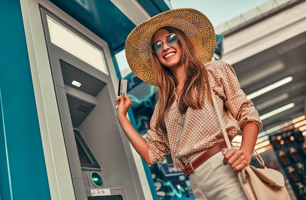 Attractive girl tourist in sunglasses, a blouse and a straw hat uses a credit card near the atm. the concept of tourism, travel, leisure.