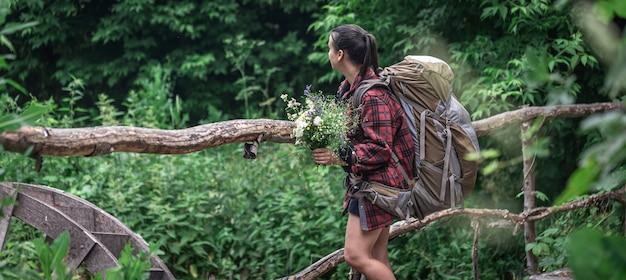 Привлекательная туристическая девушка с большим рюкзаком для путешествий и с букетом полевых цветов.