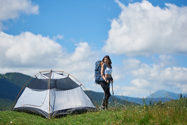 Attractive girl tourist with backpack and trekking sticks near tent on the top of a hill against blue sky and clouds, smiling, looking away, enjoying summer morning in the mountains.