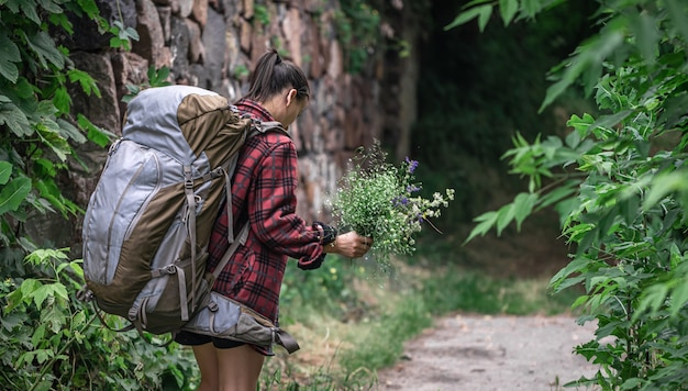 Attractive girl tourist with a large backpack for travel and with a bouquet of wildflowers.