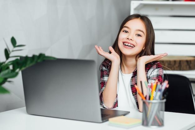 彼女の自由な時間に自宅でラップトップを使用して魅力的な女の子