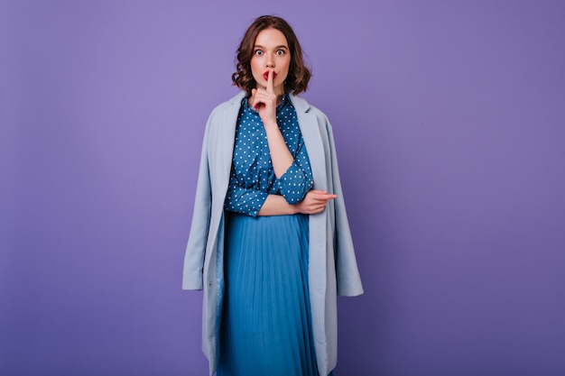 Attraente ragazza in abito vintage in posa con muro viola. la foto dell'interno della signora riccia ispirata in cappotto blu vuole il silenzio.