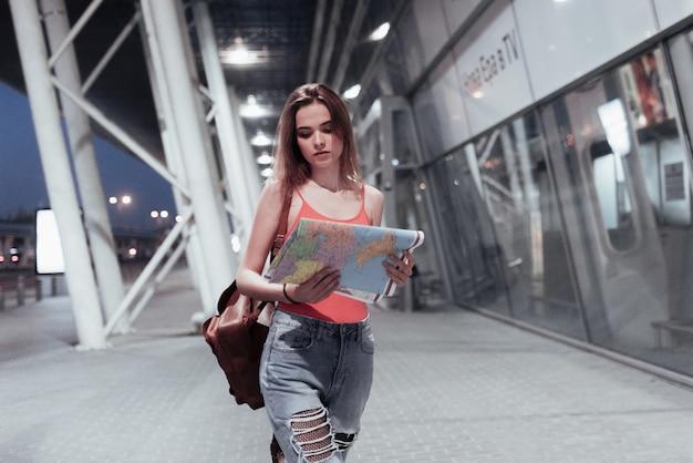 공항 근처를 걷고 그녀의 손에 있는지도를보고 매력적인 소녀