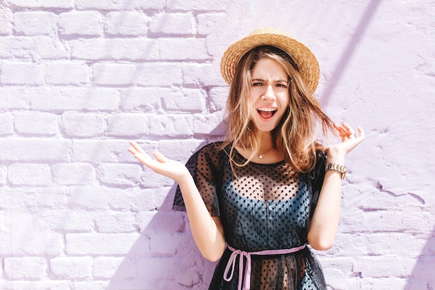 Attraente ragazza indossa cappello estivo e orologio da polso in posa con i palmi rivolti verso l'alto e l'espressione del viso incredulo
