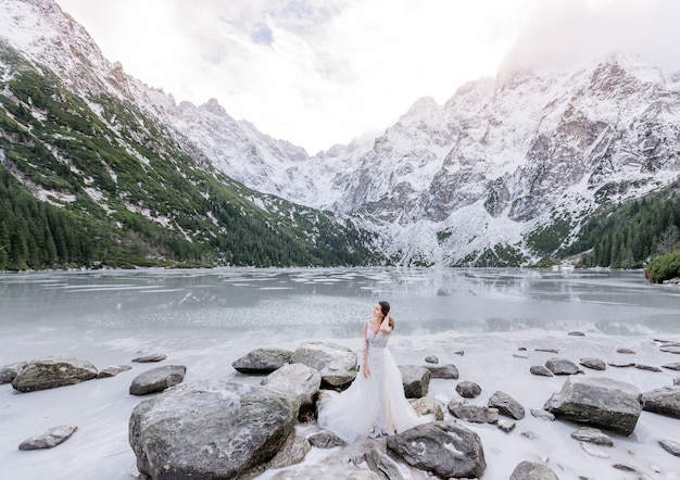 Attractive girl in white dress is standing in front of frozen lake surrounded with snowy mountains