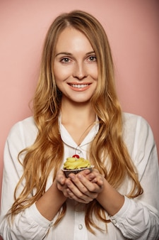 Attractive girl in a white shirt is holding cupcakes