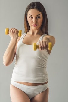 Attractive girl in white underwear is holding dumbbells