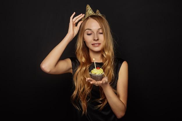 Привлекательная девушка с короной и кекс