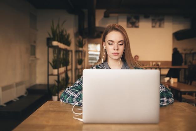カフェでノートパソコンを持つ魅力的な女の子は、ヘッドフォンで音楽を聴き、画面を見ます