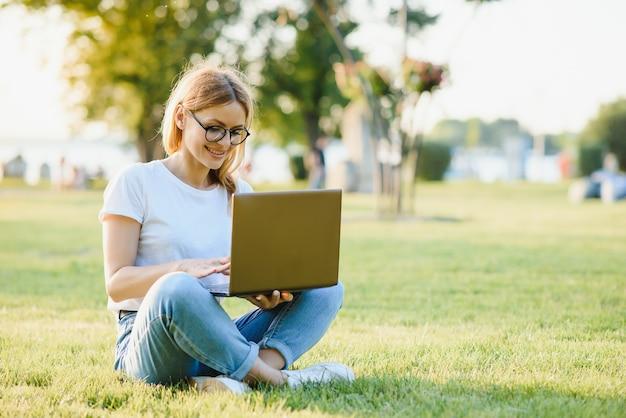 公園でラップトップを持つ魅力的な女の子