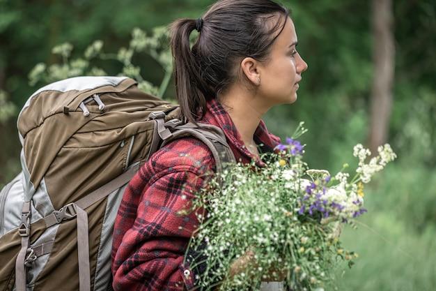 Привлекательная девушка с большим туристическим рюкзаком и букетом полевых цветов.