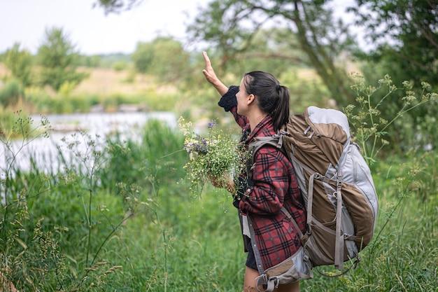 大きな旅行用バックパックと野花の花束を持つ魅力的な女の子。
