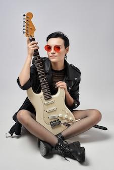 Привлекательная девушка с электрогитарой в кожаной куртке и в красных очках в студии на белом фоне