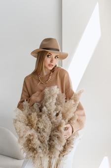 明るいスタジオでスタイリッシュな秋の服を着て秋のメイクで魅力的な女の子