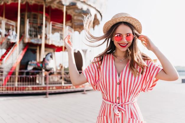 놀이 공원에서 장난하는 아름 다운 미소로 매력적인 여자. 회전 목마 옆에 그녀의 머리를 가지고 노는 밀짚 모자에 세련된 금발 아가씨의 야외 사진.