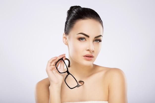 Привлекательная девушка с закрытыми черными волосами, большими глазами, густыми бровями и обнаженными плечами, держит очки и позирует в серой студии