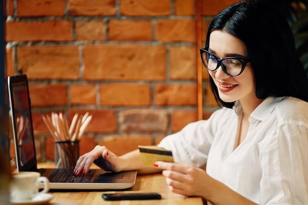 Привлекательная девушка с черными волосами в очках, сидя в кафе с ноутбуком, мобильным телефоном, кредитной картой и чашкой кофе, внештатной концепцией, в белой рубашке.