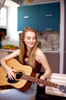 Attractive girl with blond hair plays an acoustic guitar sitting on a sofa in an apartment. music lessons concept